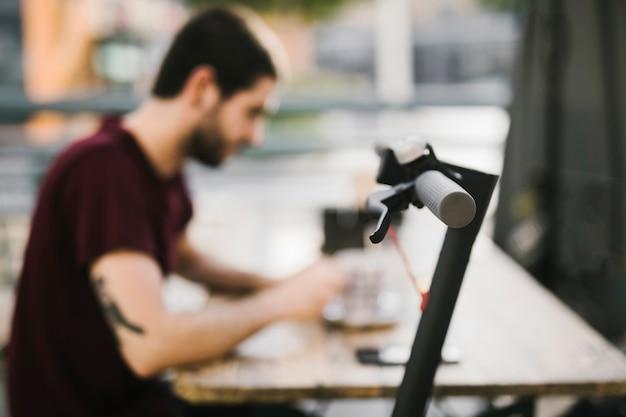 Close-up e-scooter handvat met onscherpe man