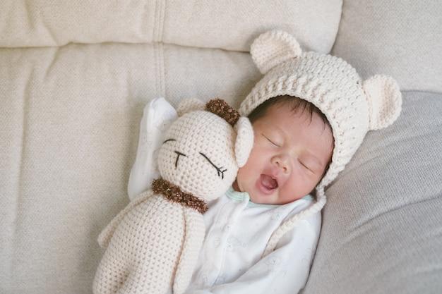 Close-up een baby die comfortabel op bank met berenpop slaapt