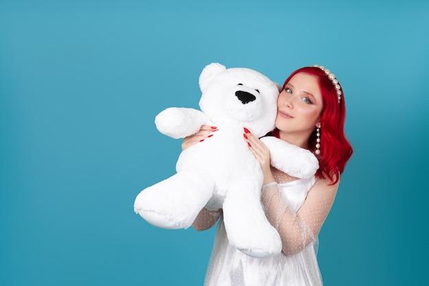 Close-up: een gelukkige tevreden vrouw in een witte jurk drukt een grote witte teddybeer tegen haar gezicht
