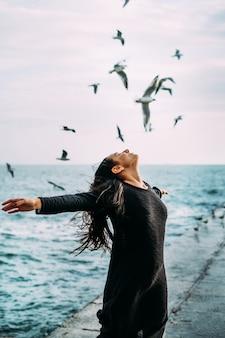 Close-up een jong meisje in zwarte kleding staat aan zee met een sterke wind.
