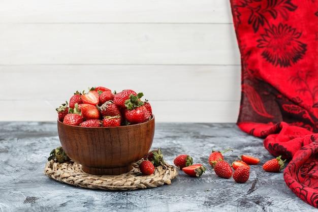 Close-up een kom aardbeien op ronde rieten placemat met rode sjaal op donkerblauw marmer en wit houten bordoppervlak. horizontale vrije ruimte voor uw tekst