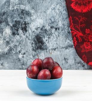 Close-up een kom pruimen met rood gordijn op witte houten plank en donkerblauw marmeren oppervlak. verticale vrije ruimte voor uw tekst