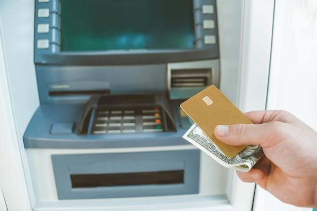 Close-up, een man houdt in zijn hand een bankkaart met geld. tegen de achtergrond van een geldautomaat.