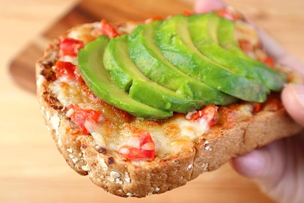 Close-up een overheerlijke gegrilde kaas toast met tomaat en gesneden verse avocado in de hand