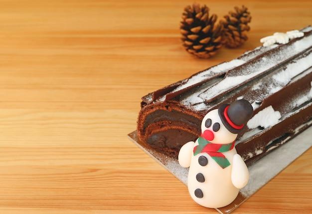 Close-up een schattige sneeuwpop marsepein van christmas roll cake op houten tafel met droge dennenappels