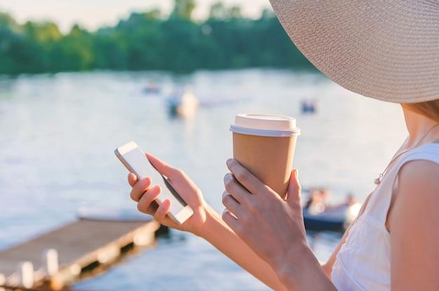 Close-up, een smartphone met een mok koffie in de handen van een meisje. op de achtergrond is er een dijk met water en jachten, boten, catamarans.
