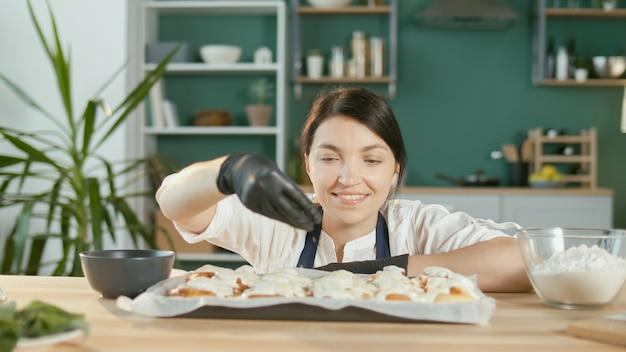 Close-up een tevreden vrouwelijke banketbakker bestrooit amandelen op de geglazuurde broodjes
