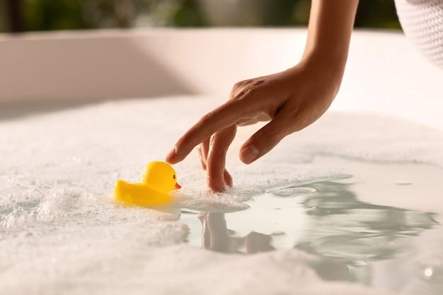 Close-up een vrouwelijke hand met zachte manicure raakt een gele rubberen eend in een schuimbad