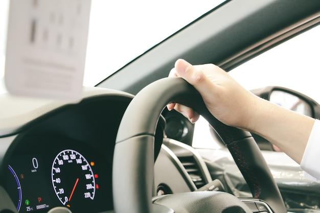Close-up een zakenman handen zet een horloge holding stuurwiel met rode console. rijden auto concept. veilig rijconcept.
