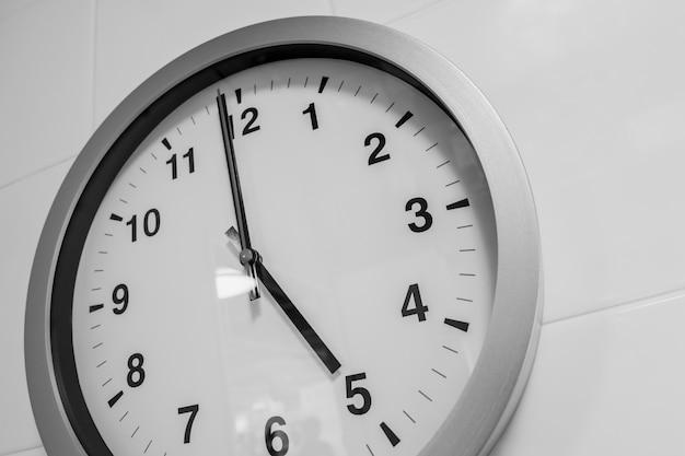 Close-up eenvoudige klok op witte muurtijd om 5 uur