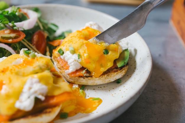 Close-up eggs benedict met zalm en avocado gesneden door mes, geserveerd met salade in witte plaat.