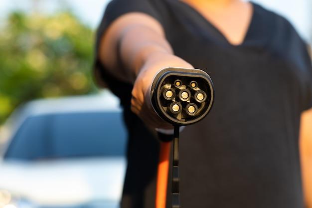 Close-up elektrische auto stekker vrouw hand voor opladen plug in hybride auto thuis of laadstation.