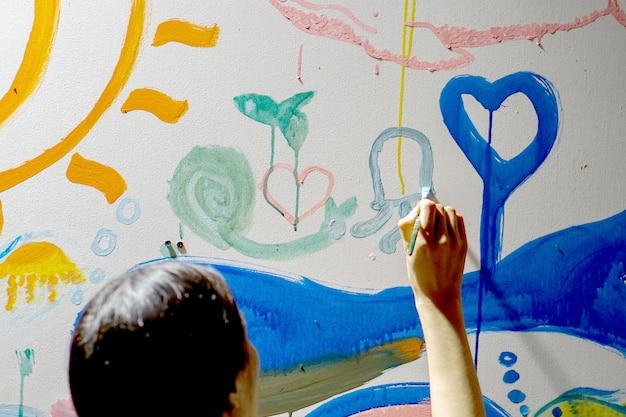 Close-up en achteraanzicht van aziatisch meisje dat en de muren van haar nieuw kunstklaslokaal trekt verfraait