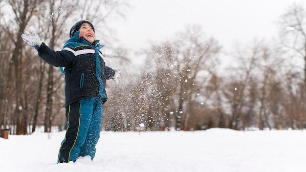 Close-up en gelukkig kind spelen in de sneeuw