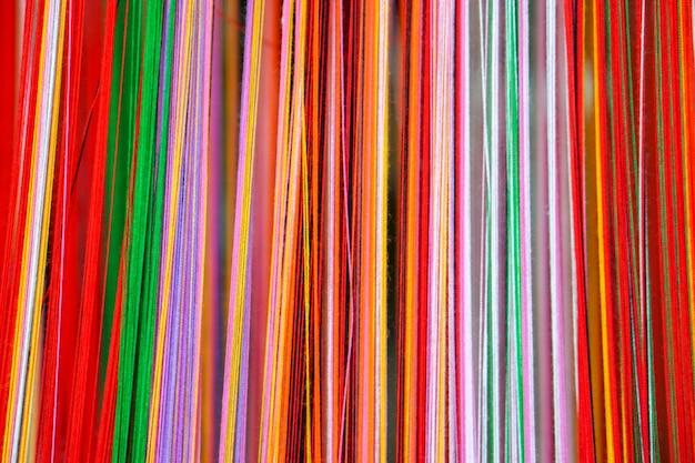 Close-up en gewas kleurrijke garens voor geweven stoffen achtergrond en textuur.