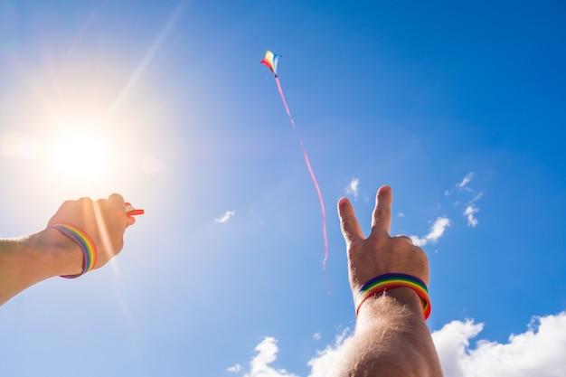 Close-up en portret van armen en handen die een armband van lgtb-kleuren dragen en een vlieger in de lucht vliegen