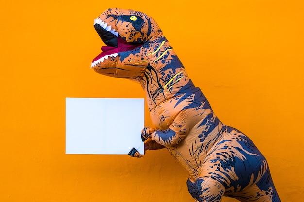 Close-up en portret van een t-rex die een wit papier vasthoudt om hier je tekst te schrijven - dinosaurus met een kopieerruimte