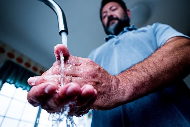 Close-up en portret van handen van man die zijn handen thuis schoonmaakt en wast om coronavirus of covid 19 te voorkomen en veilig te zijn in quarantaine van lockdown