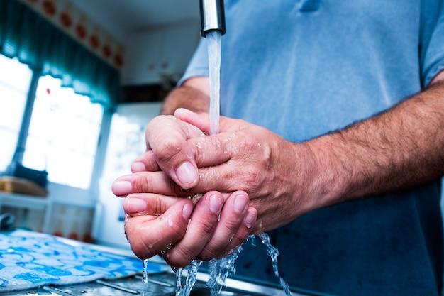 Close-up en portret van handen van volwassen man die zijn handen wast en schoonmaakt met water en zeep om coronavirus of covid 19 of elk type virus of ziekte te voorkomen