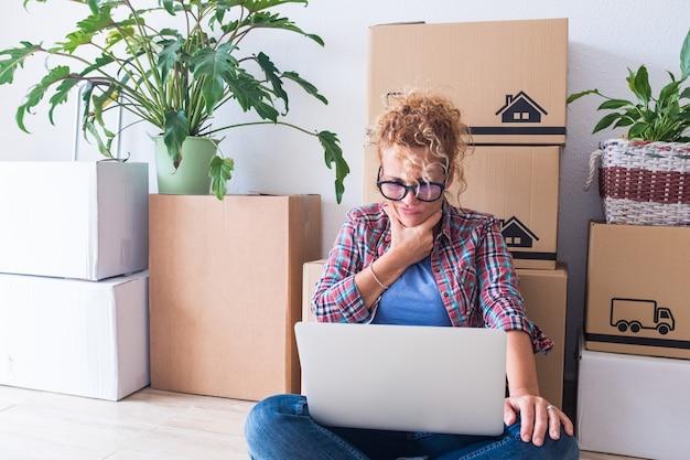 Close-up en portret van jonge vrouw thuis in een nieuw huis met dozen en pakken in haar rug - volwassen vrouw die haar laptop gebruikt maar niet begrijpt wat erin zit