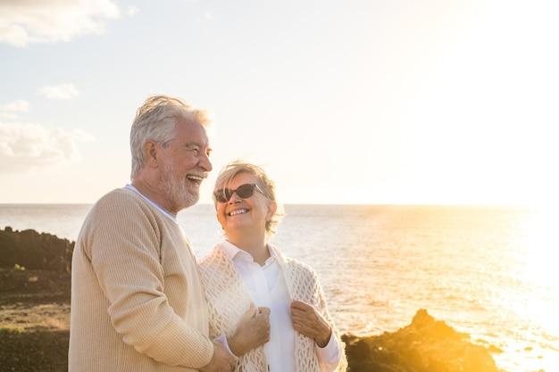 Close-up en portret van twee gelukkige en actieve senioren of gepensioneerden die plezier hebben en genieten van het kijken naar de zonsondergang die lacht met de zee - oude mensen die buiten samen van vakanties genieten