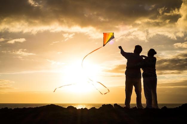 Close-up en portret van twee oude en volwassen mensen die spelen en genieten met een villende vlieger op het strand met de zee op de achtergrond met zonsondergang - actieve senioren die plezier hebben in silhouet