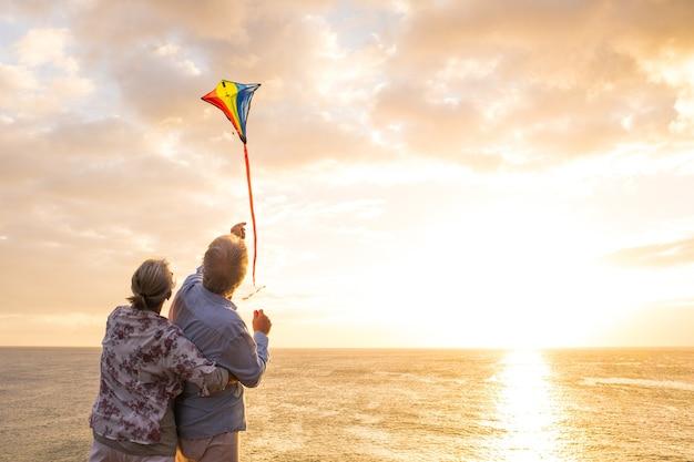 Close-up en portret van twee oude en volwassen mensen die spelen en genieten met een villende vlieger op het strand met de zee op de achtergrond met zonsondergang - actieve senioren die plezier hebben