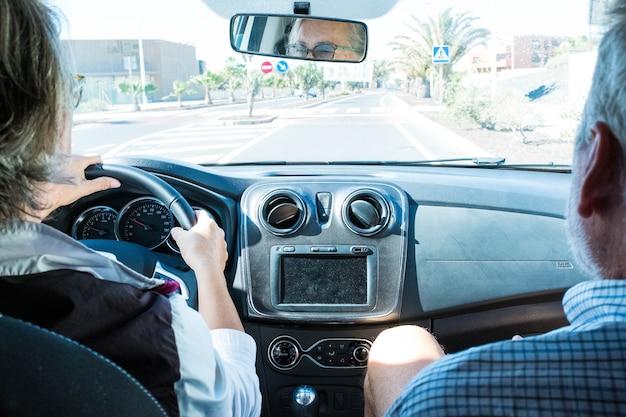 Close-up en portret van twee volwassen mensen in een auto die naar de weg of straat kijken - gepensioneerde senior die een auto bestuurt en een man die naast haar zit