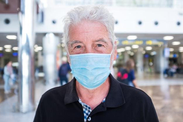 Close-up en portret van volwassen man en senior die naar de camera kijkt, ernstig bezorgd om met het virus in de lucht te reizen (covid-19) - een gepensioneerde op de luchthaven die naar de camera kijkt