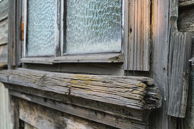 Close-up en selectieve focus op de details van een oud vintage raam met een houten muur in grunge-stijl.