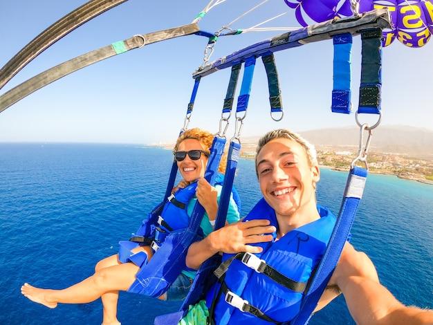 Close-up en selfie van twee gelukkige mensen die samen vliegen met een vlieger in het midden van de zee die plezier heeft - paar volwassenen die van de zomer genieten