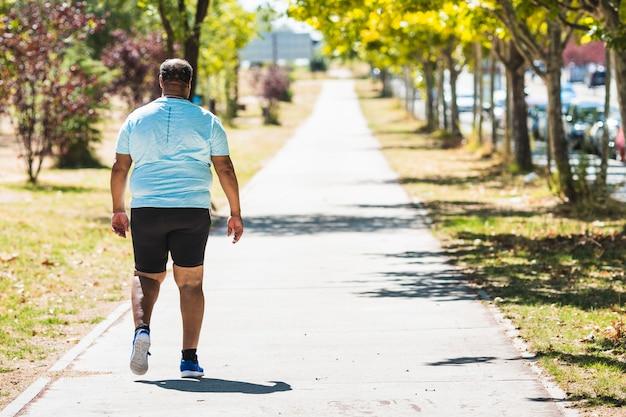 Close-up en zijaanzicht van een zwarte man met morbide obesitas gekleed in sportkleding die door het park loopt
