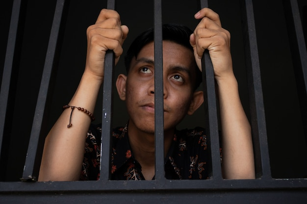 Close-up expressie van man met tralies in de gevangenis. ziet er verdrietig en verdrietig uit. concept van corruptie