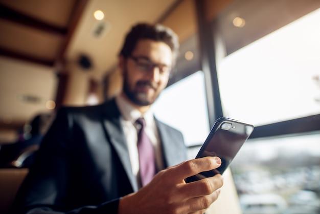 Close-up focus mobiele weergave en hand van jonge succesvolle stijlvolle gefocuste knappe bebaarde zakenman in het pak zitten in een café of restaurant in de buurt van het raam.