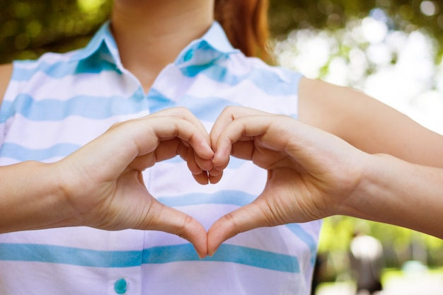 Close-up focus op gebaar handen meisje maakt liefde vorm