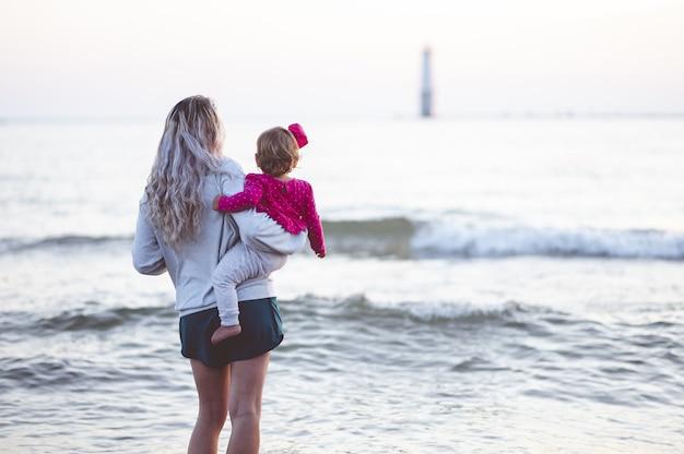 Close-up focus shot van achteren van een moeder en haar kind kijken naar de zee