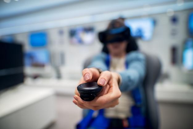 Close-up focus weergave van draadloze joystick en handen van een speels meisje tijdens het testen van vr-bril in een tech-winkel.