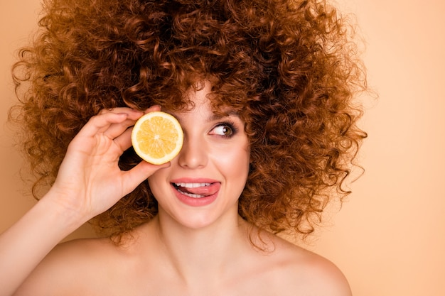 Close-up foto mooie dame oog verbergen achter schijfje limoen citroen tong uit de mond