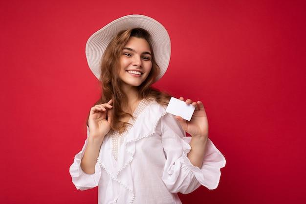Close-up foto shot van aantrekkelijke positieve lachende jonge donkere blonde vrouw, gekleed in witte blouse en witte hoed geïsoleerd op rode achtergrond met creditcard kijken naar camera
