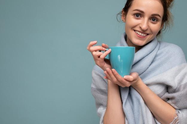 Close-up foto shot van mooie jonge gelukkig lachende brunette vrouw, gekleed in warme blauwe sjaal geïsoleerd over blauwe achtergrond blauwe mok koffie drinken en camera kijken. kopieer ruimte
