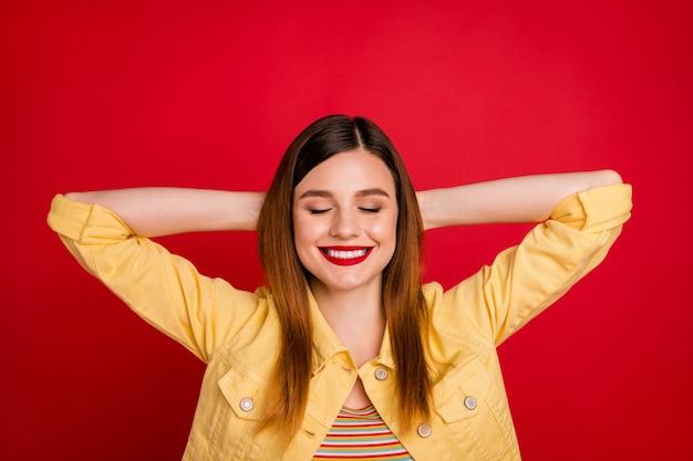 Close-up foto van aantrekkelijke dame hand in hand achter hoofd ogen gesloten brede glimlach rusten weinig dutje vrije tijd slijtage casual gele blazer jas geïsoleerd levendige rode kleur achtergrond