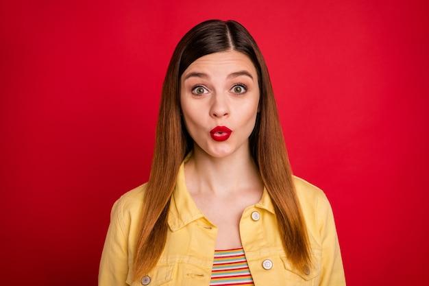 Close-up foto van aantrekkelijke grappige dame heldere pommade luisteren geweldig nieuws goed humeur vrolijke gezichtsuitdrukking slijtage casual gele denim blazer jas geïsoleerd levendige rode kleur achtergrond