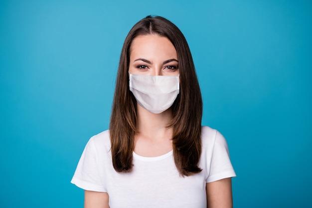 Close-up foto van aantrekkelijke mooie dame goed humeur charmant schattig recht kapsel draag casual wit t-shirt medisch masker geïsoleerd blauwe kleur achtergrond