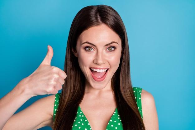 Close-up foto van aantrekkelijke opgewonden dame verhogen arm duim vinger omhoog uiting van overeenkomst die geweldige productkwaliteit goedkeurt, slijtage casual groen gestippeld hemd geïsoleerd blauwe kleur achtergrond