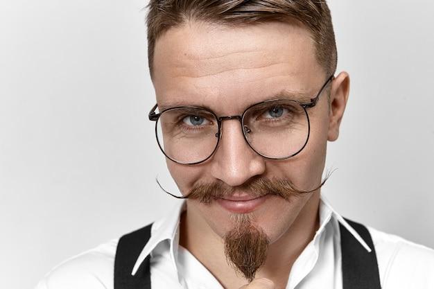 Close-up foto van aantrekkelijke positieve bankier met stuursnor, sik, baard en slimme blauwe ogen