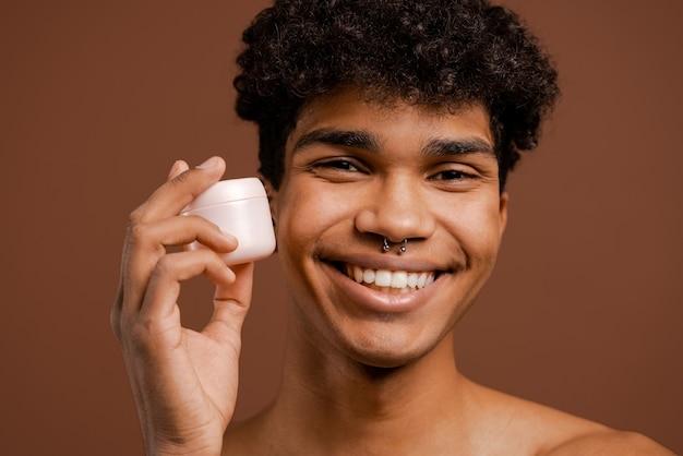 Close-up foto van aantrekkelijke zwarte man met piercing houdt voedingscrème voor gezicht. naakte torso, geïsoleerde bruine kleurenachtergrond.