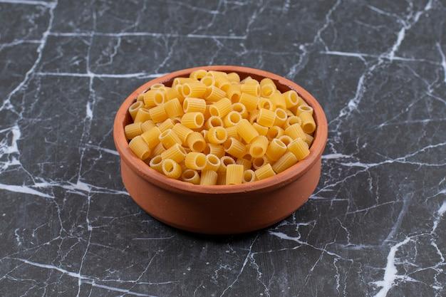 Close-up foto van aardewerk vol met rauwe pasta.