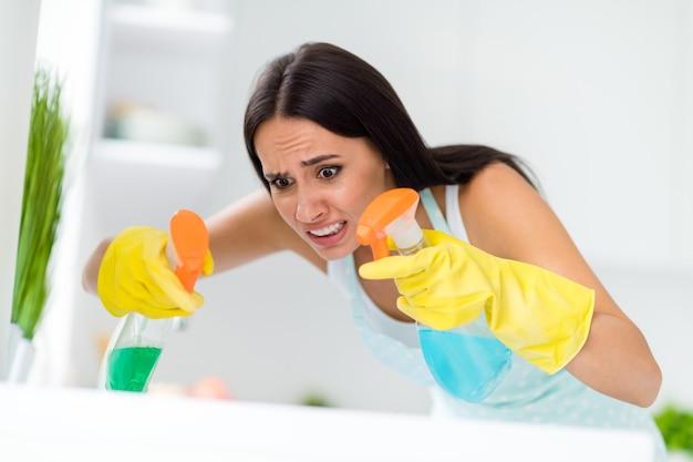 Close-up foto van angstig meisje wilt glans perfect bureau vinden vuil stof niet schoon poetsmiddel gebruik twee spray voel nerveus boos in huis keuken binnenshuis