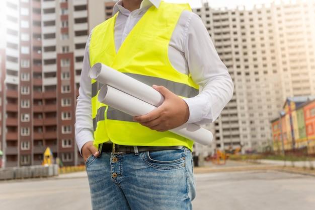Close-up foto van architect in veiligheidsvest poseren met blauwdrukken bij nieuwe gebouwen