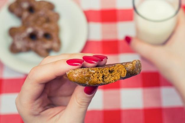 Close-up foto van biiten cookie in de hand van de vrouw en glas melk op de achtergrond